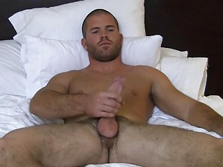 Muscled bald gay shut off wanks his big fast cock on bed